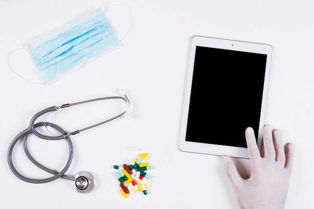 Hand die digitale tablet met masker houdt; stethoscoop en kleurrijke capsules op witte achtergrond