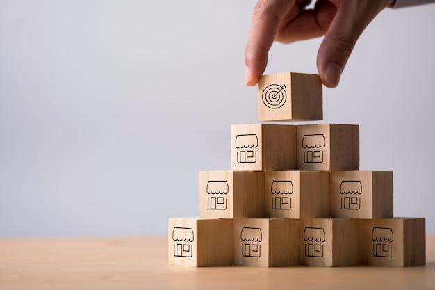 Hand die doel op verscheidene winkel zet die het scherm op houten kubus drukt. uitbreiden van bedrijfsinvesteringen en franchise-concept.