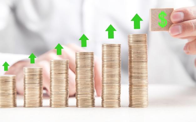 Hand die dollarteken op houten kubus toont. pijlen op munten