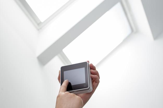 Hand die een afstandsbediening van een dakvensters op binnen bedient. domotica. ruimte kopiëren