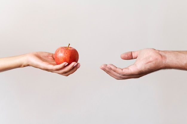 Hand die een appel aan behoeftige persoon geeft