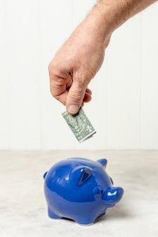 Hand die een bankbiljet in een spaarvarken zet