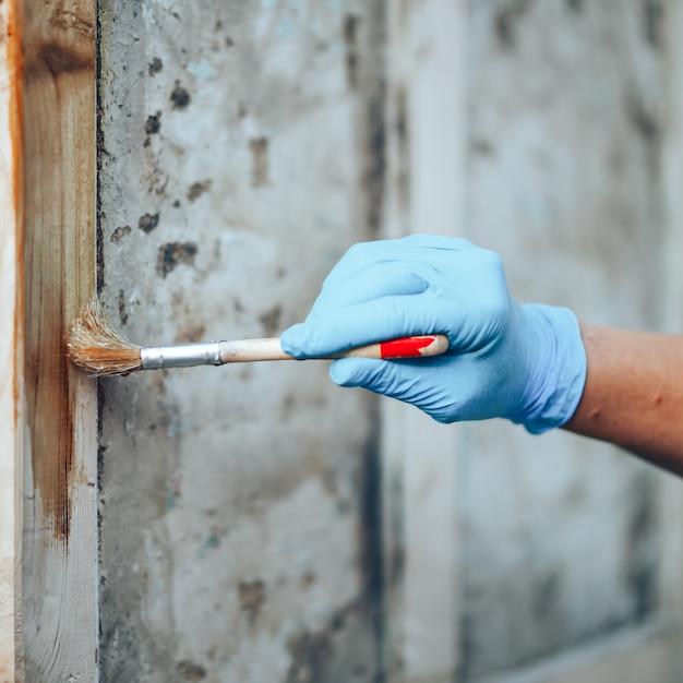 Hand die een borstel houdt die vernisverf op een houten deur toepast