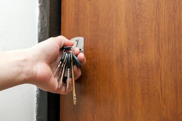 Hand die een bundel van verschillende sleutels in zeer belangrijk gat houdt