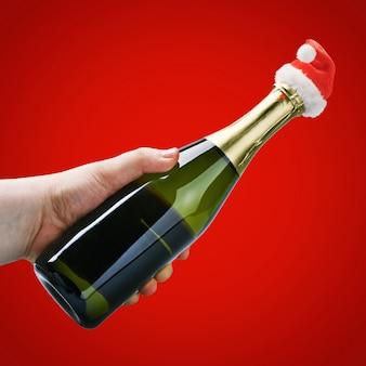Hand die een champagnefles in santa van de kerstmisdecoratie houdt