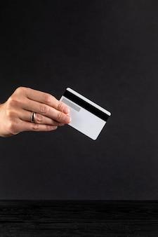 Hand die een creditcard op zwarte achtergrond houdt