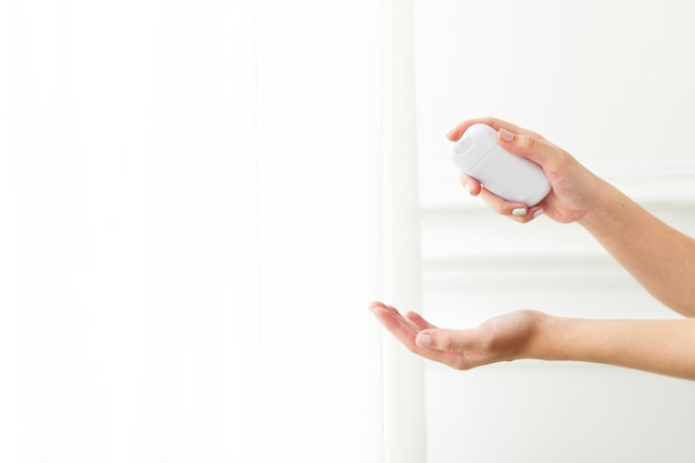Hand die een draagbaar handdesinfecterend middel gebruikt