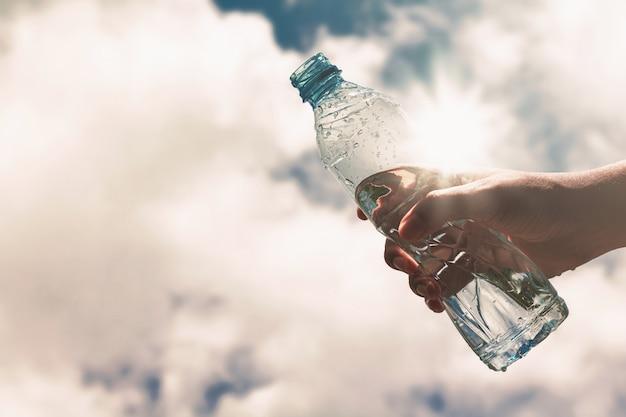 Hand die een duidelijke plastic fles zuiver drinkwater houdt