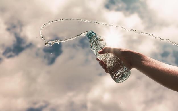 Hand die een duidelijke plastic fles zuiver drinkwater verfrist en plons houdt