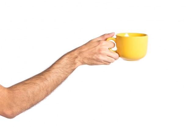 Hand die een gele koffiekopje over wit houdt