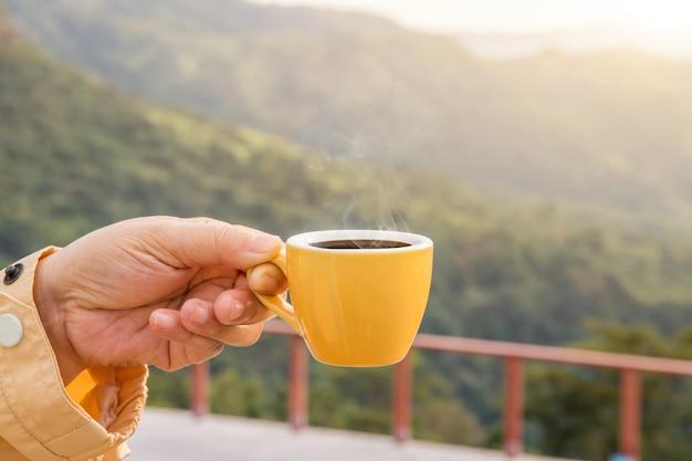 Hand die een gele kop hete espressokoffiemokken houden en aardmening van het berglandschap in de ochtend met zonlicht