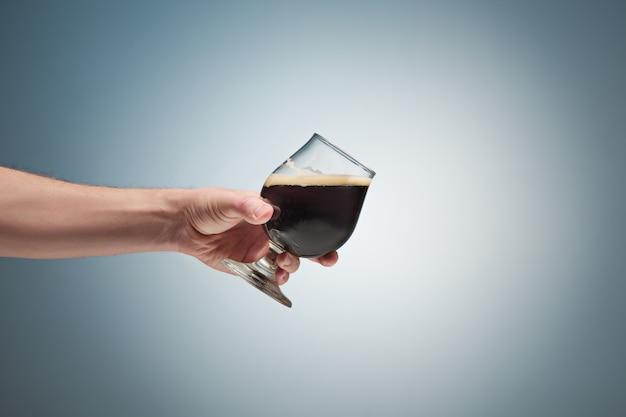 Hand die een glas bier steunt