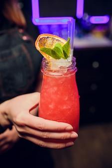 Hand die een glas met cocktail houdt