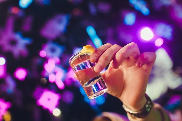 Hand die een glas met wodkaschot houdt.
