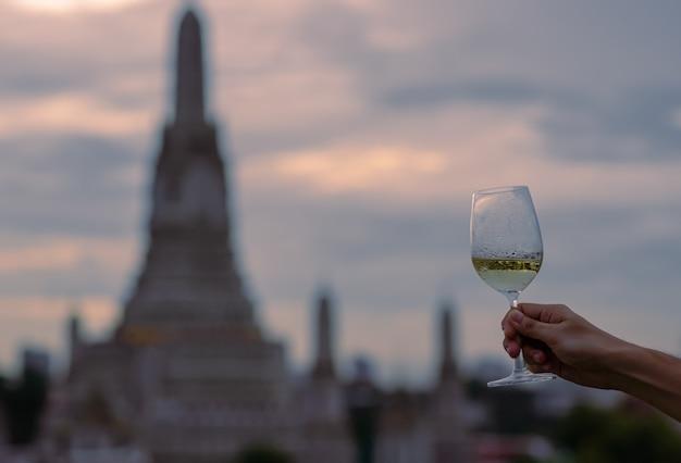 Hand die een glas witte wijn roostert met vaag van tempel