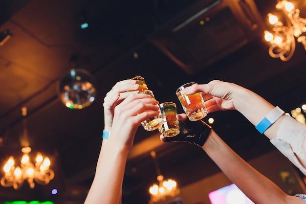 Hand die een glasschot met wodkaschot houdt.