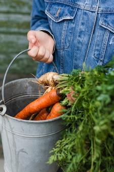 Hand die een grijze emmer met wortelen houdt