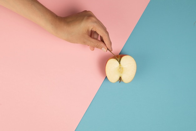 Hand die een halve appel op roze en blauwe achtergrond houdt