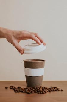 Hand die een herbruikbare koffiekop opent