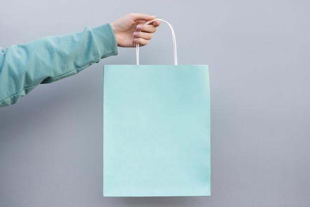 Hand die een het winkelen papieren zak houdt