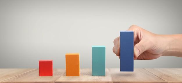 Hand die een houtblok schikt dat als grafiek stapelt. business concept groeiproces succes