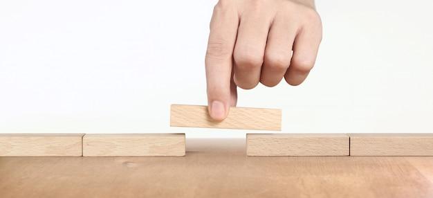 Hand die een houten blok plaatst, planning van projectbeheer in zaken