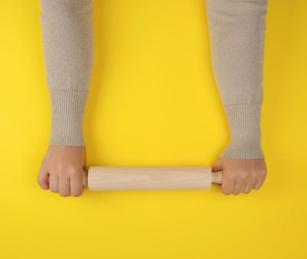 Hand die een houten deegrol houdt