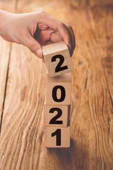 Hand die een houten kubustoren maakt met het jaar 2021