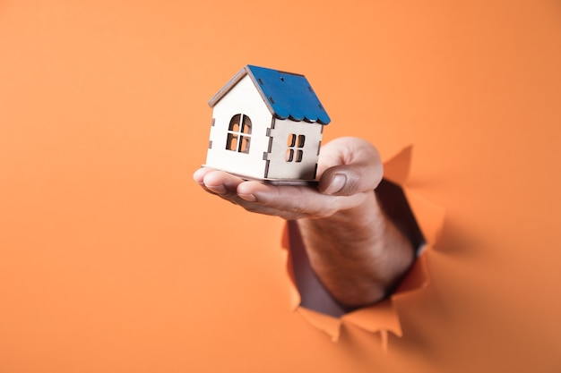 Hand die een huisminiatuur op oranje achtergrond houdt