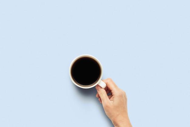 Hand die een kop met hete koffie op een blauwe achtergrond houdt. ontbijtconcept met koffie of thee. goedemorgen, nacht, slapeloosheid. plat lag, bovenaanzicht