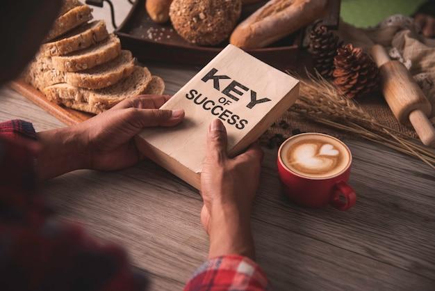 Hand die een kop van koffie houden en een boeksleutel van succes lezen - conceptenlevensstijl