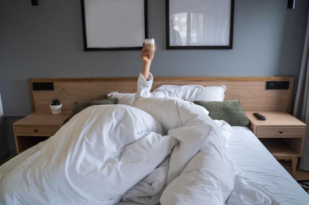 Hand die een kop van koffie thuis in bed houdt