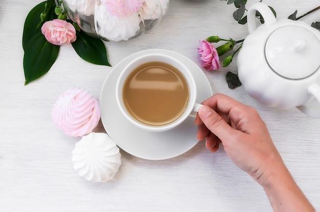 Hand die een kop van ochtendkoffie en wit en roze heemstzefier houdt. bovenaanzicht, selectieve aandacht.