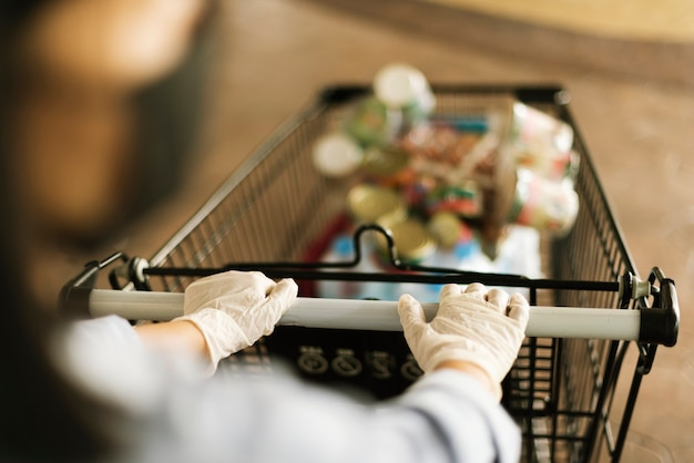 Hand die een latexhandschoen draagt terwijl hij een winkelwagentje duwt om besmetting met het coronavirus te voorkomen