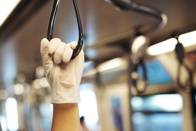 Hand die een latexhandschoen draagt terwijl u een treinleuning vasthoudt om besmetting met het coronavirus te voorkomen