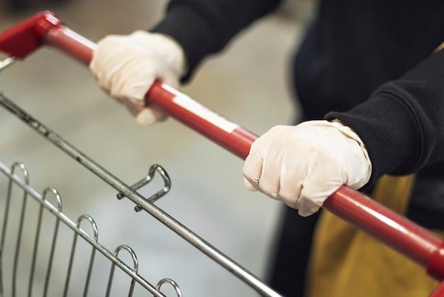 Hand die een latexhandschoen draagt tijdens het duwen van een winkelwagentje om besmetting met het coronavirus te voorkomen