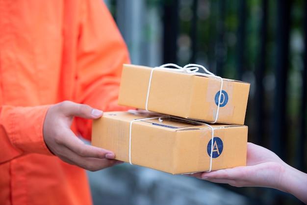 Hand die een leverings bruine vakjes van het concept van de bezorgerlevering goedkeurt