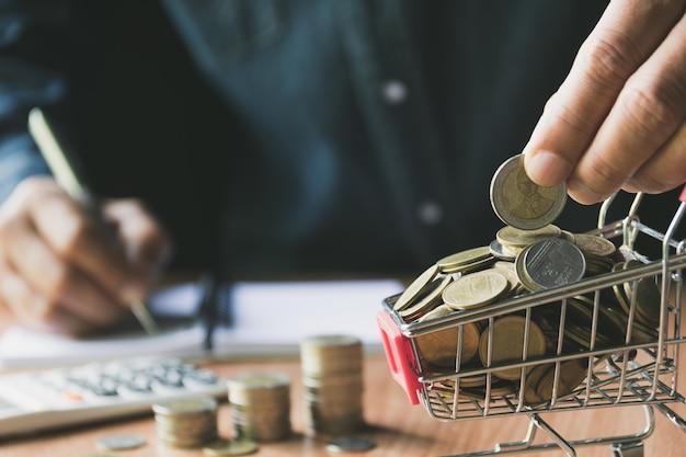 Hand die een muntstuk met stapel van muntstuk in het boodschappenwagentje voor boekhoudings en bedrijfsconcept houdt.