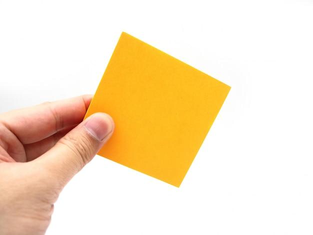 Hand die een oranje nota van de document stok houdt die op een witte achtergrond wordt geïsoleerd.