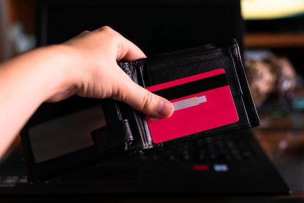 Hand die een portefeuille en een creditcard met laptop houdt