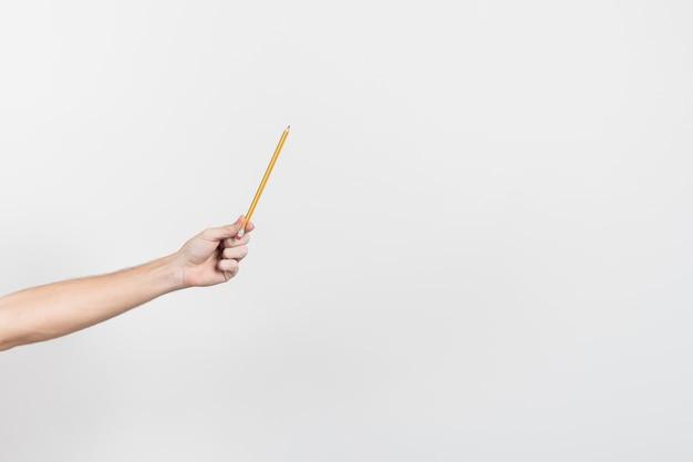Hand die een potlood met exemplaar ruimteachtergrond houdt