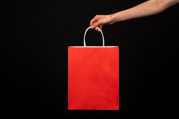 Hand die een rode het winkelen zak houdt