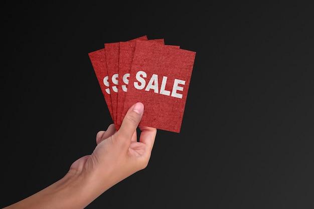 Hand die een rode kaart met tekstverkoop houdt