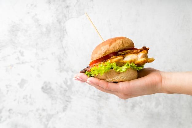 Hand die een smakelijke hamburger houdt