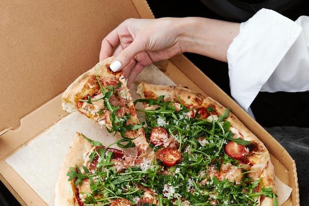 Hand die een stuk italiaanse keukenpizza neemt taking