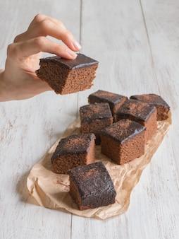 Hand die een stuk van vers gebakken brownie houdt