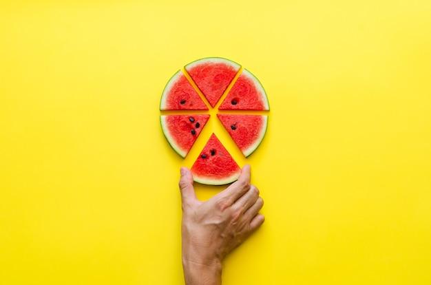 Hand die een stuk watermeloen neemt dat als pizza snijdt. minimaal zomerconcept.