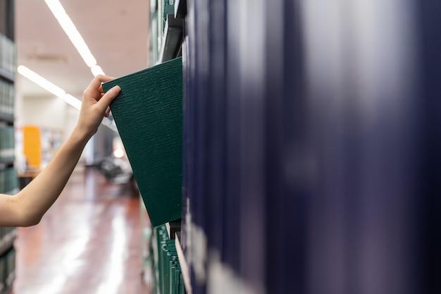 Hand die een thesis-boek van de plank in bibliotheek trekt. groene kleurenboeken.