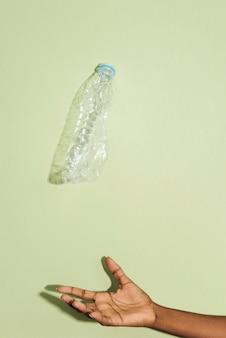 Hand die een vallende verpletterde plastic fles opvangt
