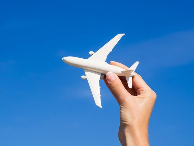 Hand die een vliegtuig in de lucht houdt